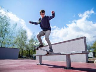 Skater doing croocked grind trick on bench in skatepark