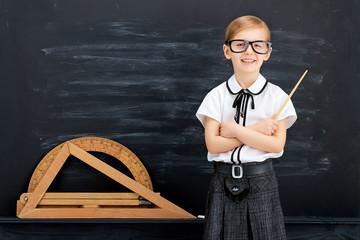 Little girl against blackboard. School concept
