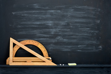 Chalk rubbed out on blackboard and vintage wooden geometric measures
