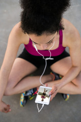 Young jogger with earphoes and cell phone having a rst