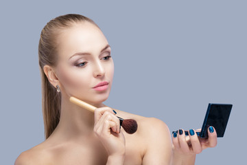 beautiful blond woman holding makeup brush and looking in the mirror on a gray background.