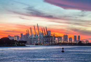 Dramatic landscape at sunset with sunshine between clouds at Miami industrial harbour - Florida United States