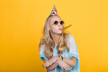 portrait of funny blond woman in birthday hat and blue shirt on yellow background. Celebration and party.