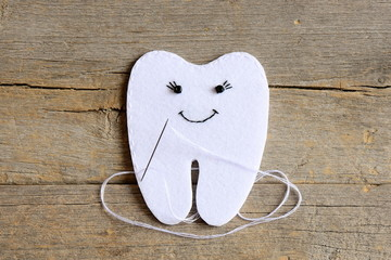 How to sew a felt tooth fairy. Step. Instruction for kids. Join the felt edges of felt tooth fairy with white thread. Vintage wooden background. Simple sewing projects and handmade crafts. Top view