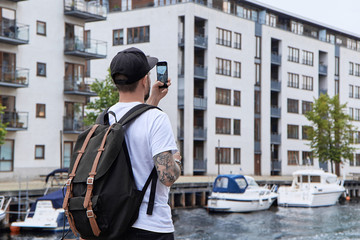 Young hipster man with backpack, taking picture of street on smart phone at journey in Copenhagen, city tourism