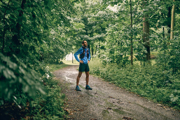 Fit male jogger day training for cross country forest trail race in a rain nature park.
