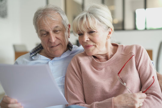 Senior couple in sofa reading official documents