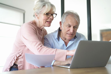 Senior couple at home connected on internet with laptop