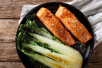 Glazed salmon fillet with sesame seeds and roasted cabbage bok choy close-up. horizontal top view