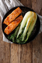 Glazed salmon fillet with sesame seeds and roasted cabbage bok choy close-up. Vertical top view