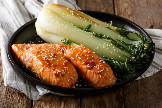 Glazed salmon fillet with sesame seeds and roasted cabbage bok choy close-up. horizontal