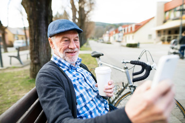 Senior man with bicycle in town, taking selfie with smart phone