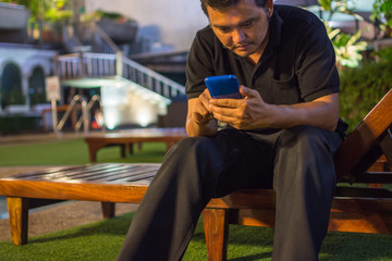 Asia man smiling using smartphone at poolside