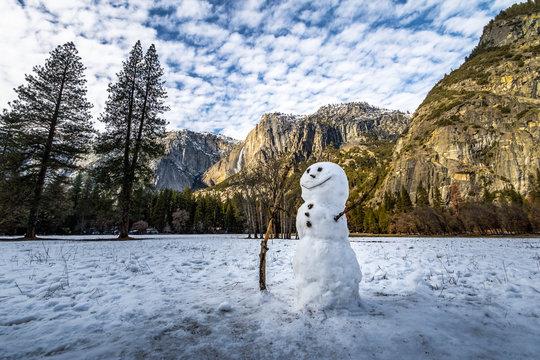 Snowman at Yosemite Valley during winter with Upper Yosemite Falls on background - Yosemite National Park, California, USA