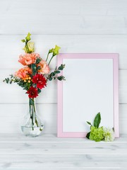 Flowers in vase and a photo frame on a wooden background.