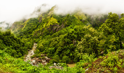 Panoramic view of the green mountains in the fog, jungle and river