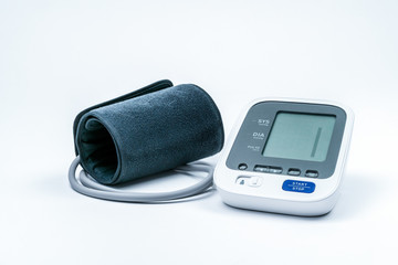 Automatic portable blood pressure machine with arm cuff isolated on white with copy space, studio shot.