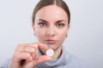 Attractive girl taking a pill on light background