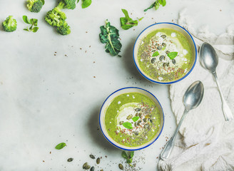 Spring broccoli green cream soup with mint and coconut cream in bowls over light grey marble background, top view, copy space. Clean eating, dieting, vegan, vegetarian, healthy food concept