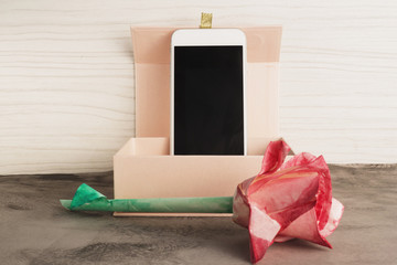 Origami watercolor rose and smart phone in rose box on vintage grey background