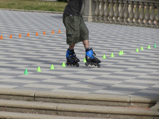 Legs of guy on rollerblades. Rollerblader and slalom cones