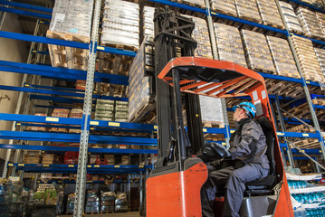 Storehouse employee during driving on forklift in warehouse