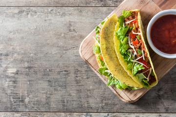 Mexican tacos on wooden background