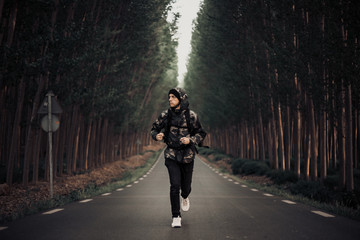 Backpacker man running on a forest road