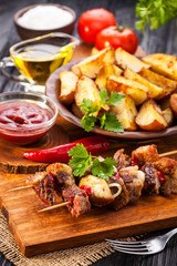 Meat skewer with herbs With onions, baked potatoes, tomatoes and greens