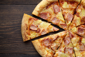 Sliced hawaiian pizza with ham and pineapple on dark wooden table.