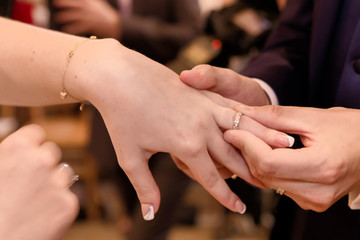 Close up hands of bride and groom putting on a wedding rings