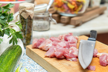 Raw pork neck meat cut in slices on wooden cutting board  in a modern kitchen. Shallow depth of field. Toned