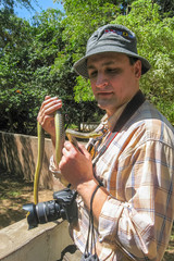 Photographer stands with snake tied like cravat on his neck. Arusha, Tanzania, Africa.