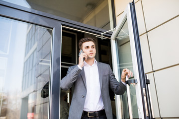Serious business man in suit talking on phone in office and holding the door