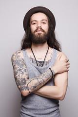 tattoed handsome bearded man in hat