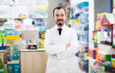 Glad male pharmacist suggesting useful drug