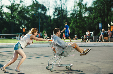 Happy love couple having fun  with a supermarket trolley