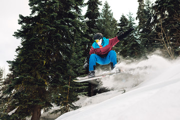 snowboarder is jumping and freeriding in the mountain forest