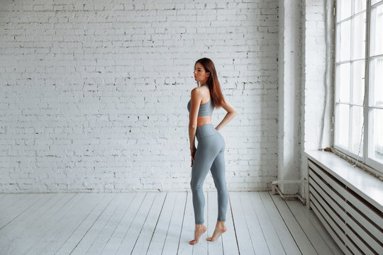 Girl in tight clothes yoga and fitness. Gray leggings with high waist