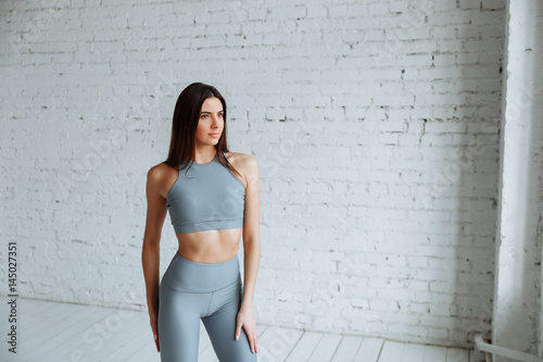 67b5019826592 Girl in tight leggings with high waist and sporting a short top on a  background of white brick wall