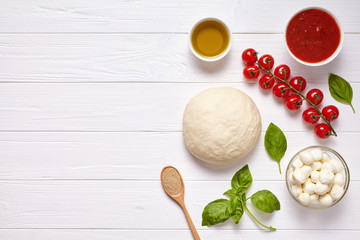Raw pizza dough with baking ingredients: mozzarella cheese, tomatoes sauce, basil, olive oil, cheese, spices. Italian margherita on wooden table. Italian pizza margarita