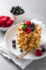 Delicious homemade waffles with fresh berries on concrete background