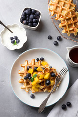 Breakfast with homemade waffles and fresh blueberries on concrete background