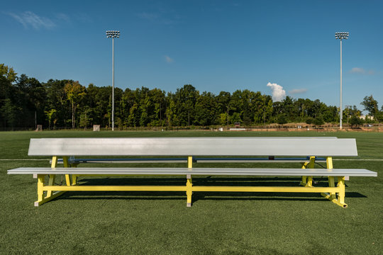 Empty aluminum bench team sports background on a green turf field