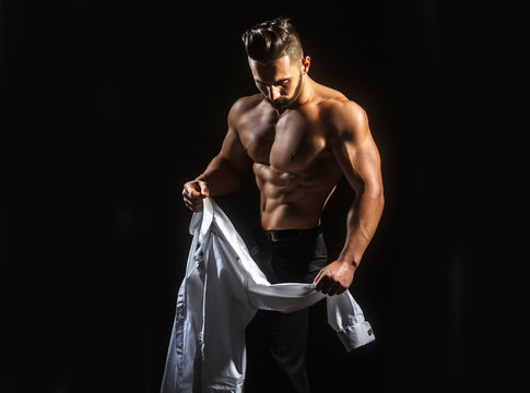 Man undresses, takes off his white shirt. Young guy with beautiful bare naked sports torso. Man wearing shirt. Sexy young  muscular man in shirt on a dark background at morning