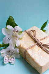Wrapped parcel with alstroemeria flowers on mint background