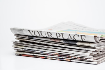 Close up of a stack of folded newspapers on white background