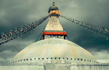 Nepal Religion Culture. Boudhanath Stupa with eyes and colorful prayer flagsin the Kathmandu valley, Nepal. Dramatic cloudy sky in the background
