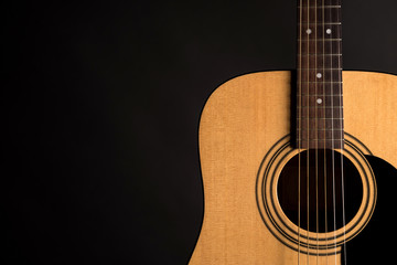 Part of a wooden acoustic guitar on the right side of the frame, on a black isolated background