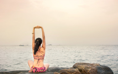 Girl doing yoga at the beach